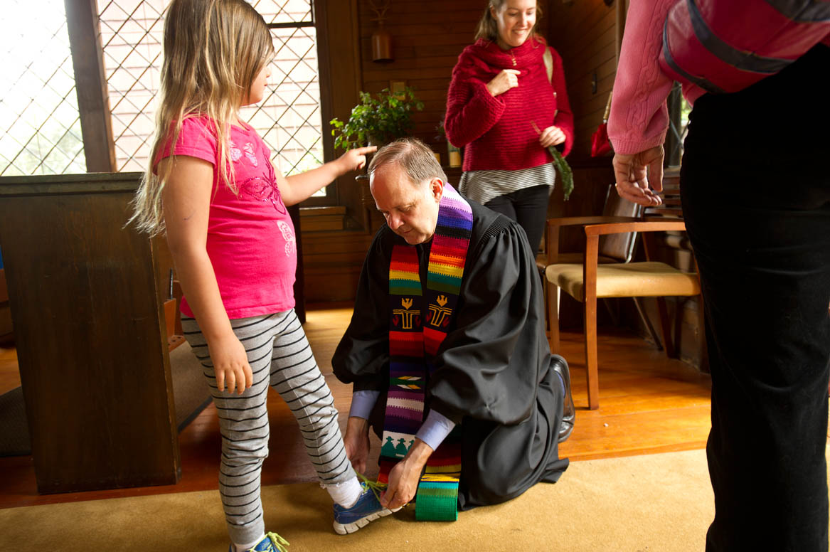 Rev. Paul Mowry ties a shoelace for his daughter Ellie Mowry-Silverman, 6, after leading a Sunday service in Sausalito