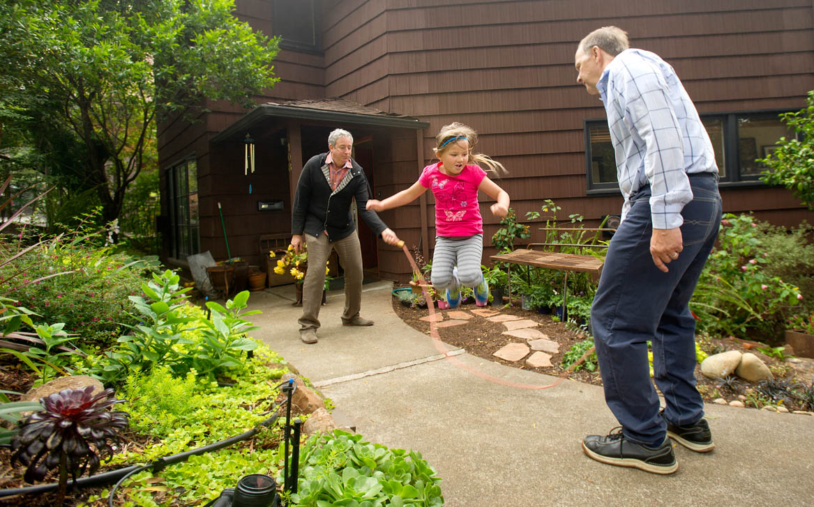 Ellie Mowry-Silverman, 6, jumps rope with her dads Rev. Paul Mowry (R) and Joe Silverman at their home in Sausalito